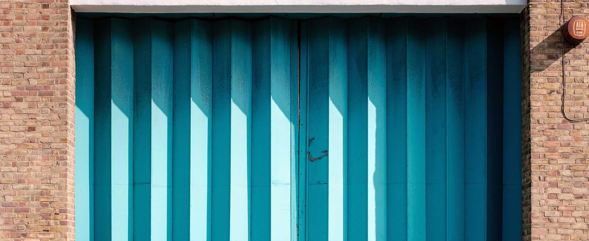 brick-building-blue-shutter-door